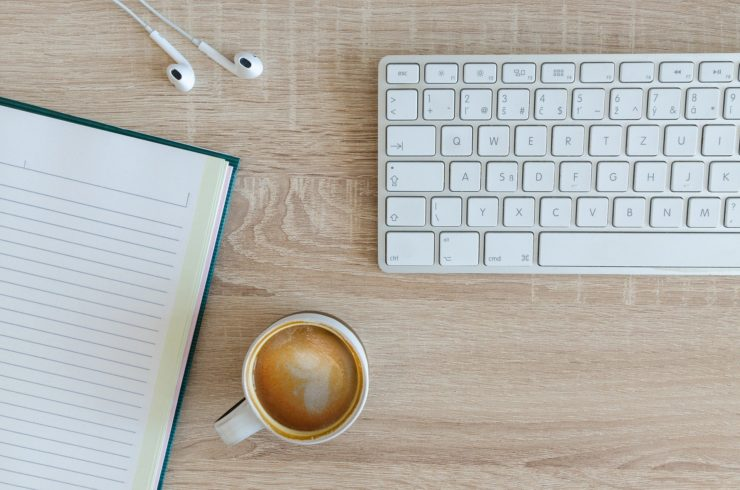 Picture of computer key board, head phones, cup of coffee and note book