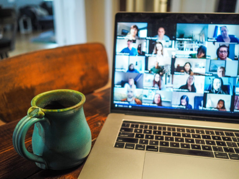 A green cup next to a lap-top. Screen showing small picture squares of persons attending a digital gathering.