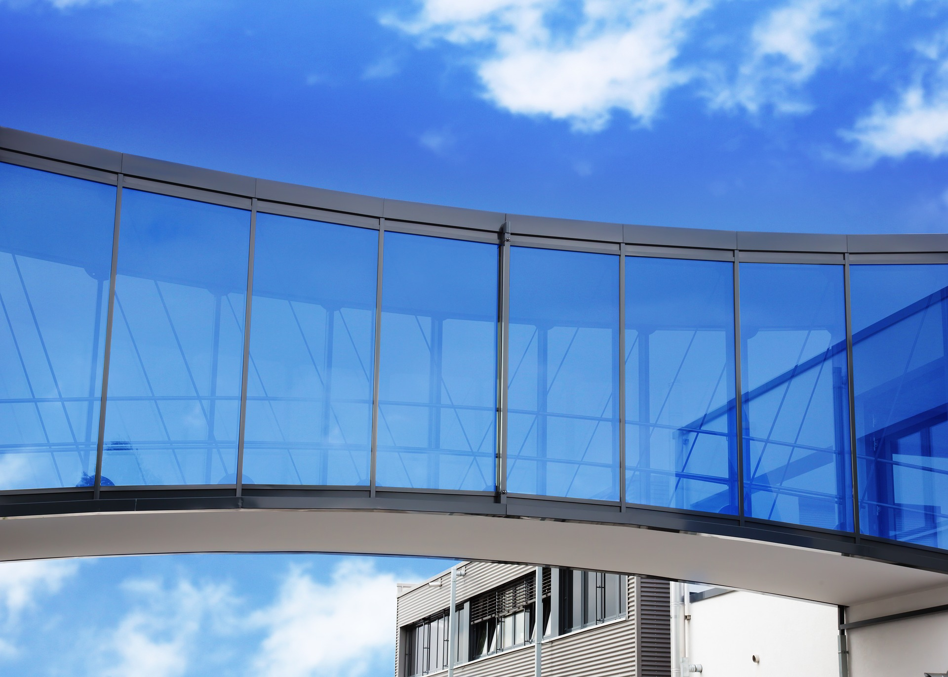 Pedestrian bridge with glass walls between two buildings against a clear blue sky.
