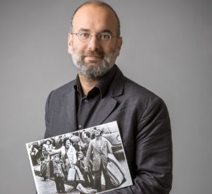 Picture of Felipe Estrada, holding a picture of his family as they arrive in Sweden in 1974. Felipe has greyish beard, wears round glasses and is dressed in a grey suit and dark-grey shirt.
