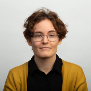 Portrait picture of PhD-student Aino Jauhiainen, Helsinki University. Aino has short, brown, curly hair and wear glasses. She is dressed in a black shirt and yellow cardigan.