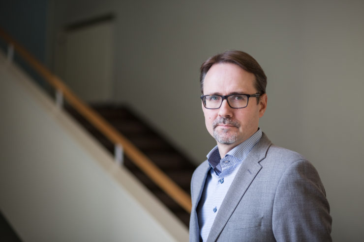Professor Janne Kivivuori, Helsinki University. He has short, brown hair and glasses. He is wearing a light grey jacket and light blue shirt. In the background there is a staircase.