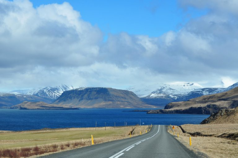 Travelling on a road in Iceland a sunny day, straight ahead view of a fjord, hills and volcanoes in the background