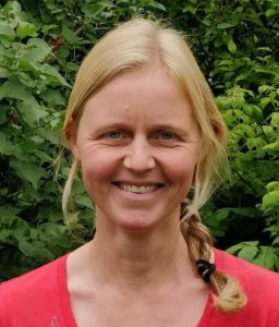 Photo of Mie Birk Haller. She is standing outside, green leaves in the background, dressed in a red t-shirt. She has blond hair in a braid and is smiling.